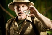 Explorer finding a huge gem in the jungle — Stockfoto