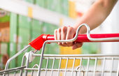 Supping cart and supermarket shelf — Stock Photo