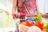 Woman at supermarket with full cart — Stock Photo