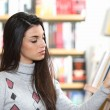 Pretty young woman looking for a book in a bookstore — Stock Photo #9036136