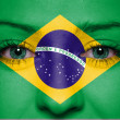 Portrait of a woman with the flag of the Brazil painted on her face — Stock Photo