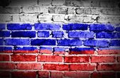 Russian flag on old brick wall background or texture — Stock Photo