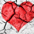 Natural red heart shape in cracked dry soil — Stock Photo