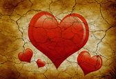 Forma de corações vermelhos naturais no solo seco rachado — Fotografia Stock
