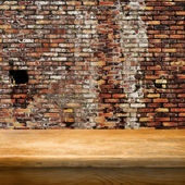 Empty table and brick wall in background. — Stock Photo