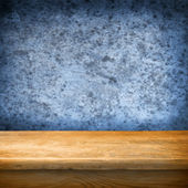 Background with wooden table and grunge blue wall — Stock Photo
