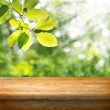 Wooden table and green forest leaves — Stock Photo #30280221