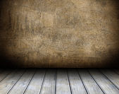 Empty wooden table and dark brown wall in background — Stock Photo