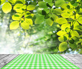 Empty table with green leaves background. — Stock Photo