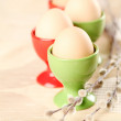 Eggs in red and green eggcups - Stock Photo