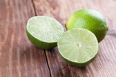 Limes on wood background — Stock Photo