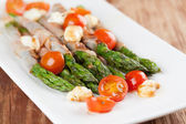 Grilled asparagus with prosciutto, mozzarella and cherry tomatoe — 图库照片