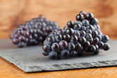 Blue grape clusters on slate board — Stock Photo