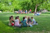 People talking and sitting on lawn — Stock Photo