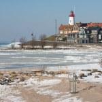 Dutch lighthouse in wintertime near a frozen sea — Stock Photo #14168138