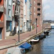 New residential area from Amsterdam along a canal with small boa - Lizenzfreies Foto