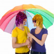 Royalty-Free Stock Photo: Funny couple with wigs, sunglasses and umbrellas