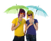 Funny couple with wigs, sunglasses and umbrellas — Stock fotografie