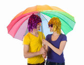 Funny couple with wigs, sunglasses and umbrellas — Stock Photo