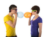 Man and woman with sunglasses blowing balloons — Stock Photo