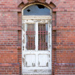 Old dilapidated door in masonry house front — ストック写真