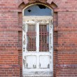 Old dilapidated door in masonry house front — Стоковая фотография