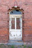 Antigua puerta ruinosa en frente de casa de mampostería — Foto de Stock