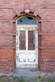 Old dilapidated door in masonry house front — Stok fotoğraf