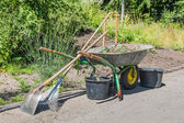 Wheelbarrow with gardening tools — Stock Photo