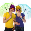 Couple with wigs, sunglasses and umbrellas — Stock Photo