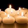 White candles on a black reflecting background — Stock Photo #32658769