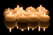 White candles on a black reflecting background — Stock Photo