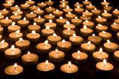 Velká skupina hořící svíčky na černém pozadí — Stock fotografie
