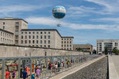 BERLIN, GERMANY - JULY 24: Remains of Berlin Wall and Welt Balloon that takes tourists 150 meters into the air above the city on July 24, 2013 in Berlin, Germany — Stock Photo