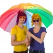Trendy couple with sunglasses and wigs covered under a rainbow unbrella — Stock Photo