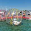 Постер, плакат: Children have fun inside plastic balloons on the water during a fishing fare