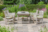 Wooden table and chairs in an ornamental garden — Stock Photo