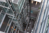 Looking downwards in a modern open elevator shaft — Stock Photo