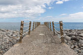 Concrete jetty and iron fence with ropes — Stock Photo
