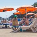 mensen zitten onder een parasol op een openbaar zwemmen bad op madeira, portugal — Stockfoto #51480497