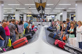 Airplane travelers waiting for their luggage at Schiphol airport in Amsterdam, The Netherlands — Stock Photo