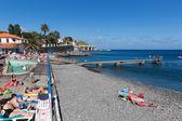 Boulevard y playa con el sol y nadar personas en madeira — Foto de Stock