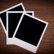 Old blank photos frames lying on a wood surface — Stock Photo #12536607