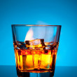 Glass of scotch whiskey and ice on a blue — 图库照片