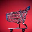 Shopping cart on red background — Stock Photo