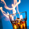 Glass of scotch whiskey and ice with fire on blue — Stock Photo
