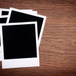 Blank photo frames on wooden background — Stock Photo