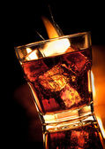 Cola with whiskey in glass and fire on black — Stock Photo