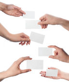 Set of hands holding empty business cards on white — Stock Photo