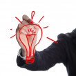 Hand with a pen drawing light bulb — Stock Photo #24484505